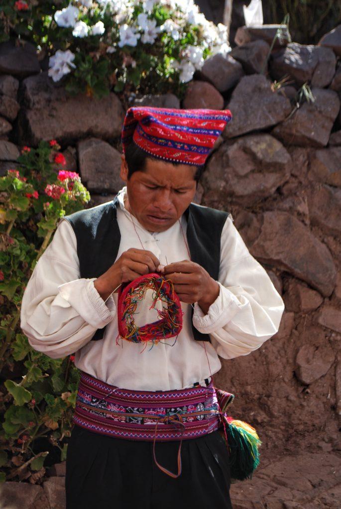 Artigiano in abiti tradizionali sull'isola di Taquile sul lago Titicaca